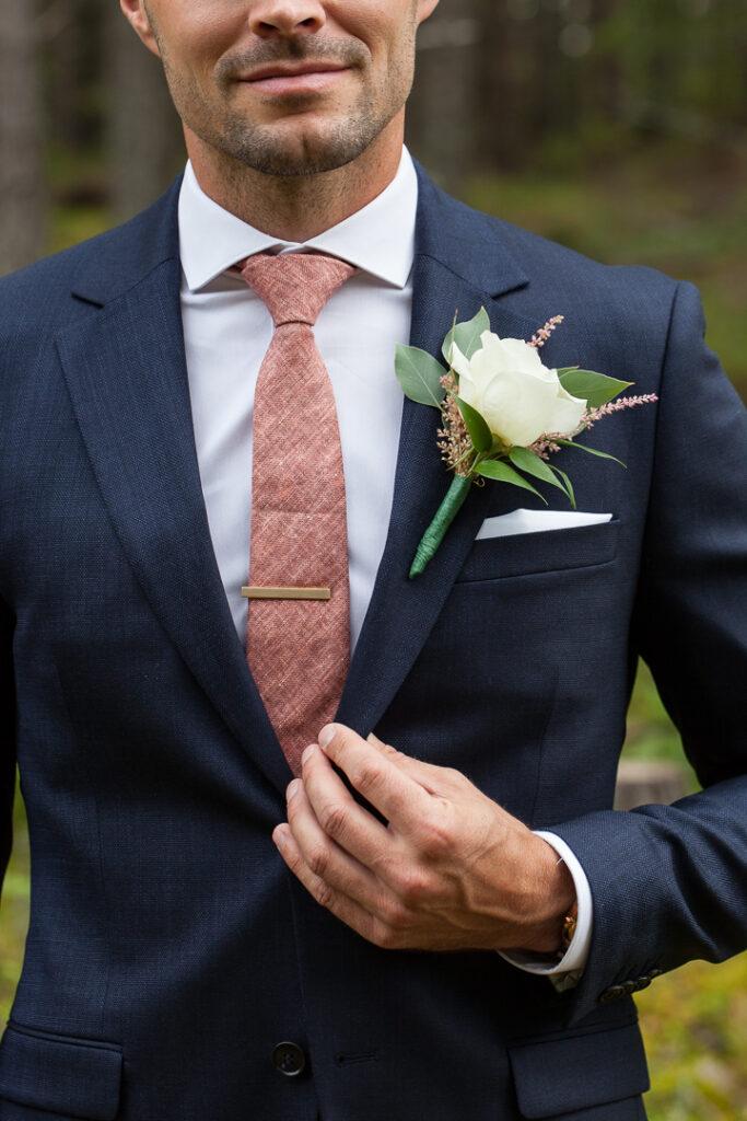 Corsagen den blomma som bärs på kavaj- eller frackslaget av brudgummen vid ett bröllop