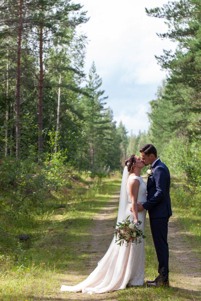 Brudparet i skogen bröllopsfotografering