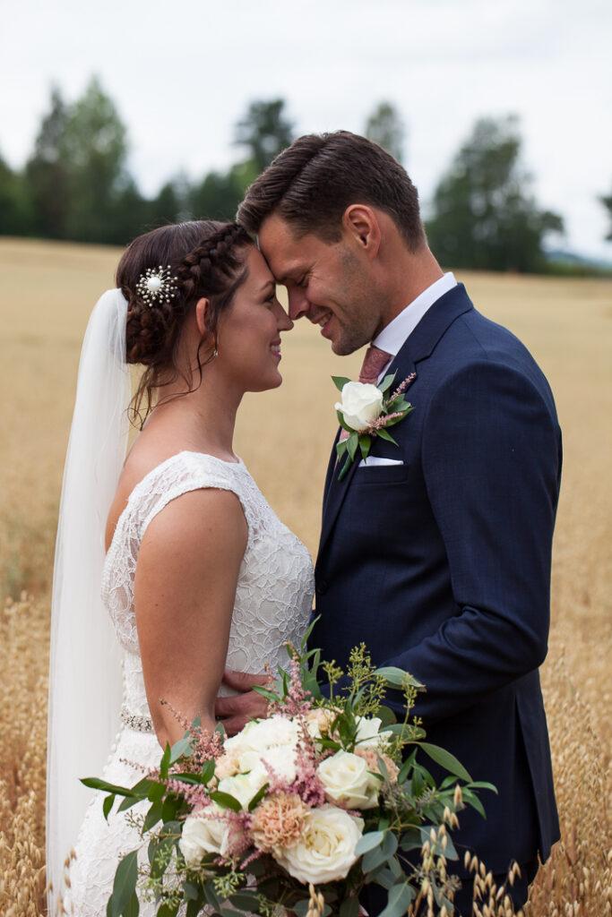 Brudparet i sädesåkern bröllopsfotografering