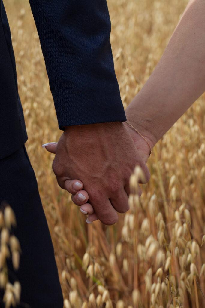 Brudparet i sädesåkern bröllopsfotografering händerna