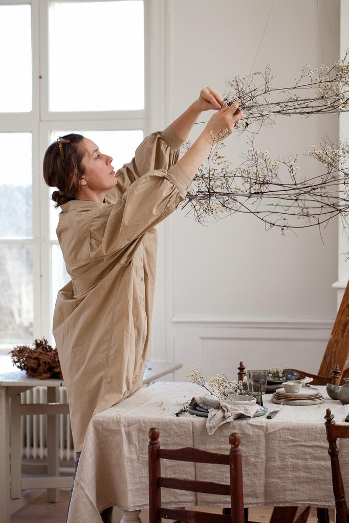 Vinterdukning i ateljen med som Maja binder krans för över bordet av skogsklematis