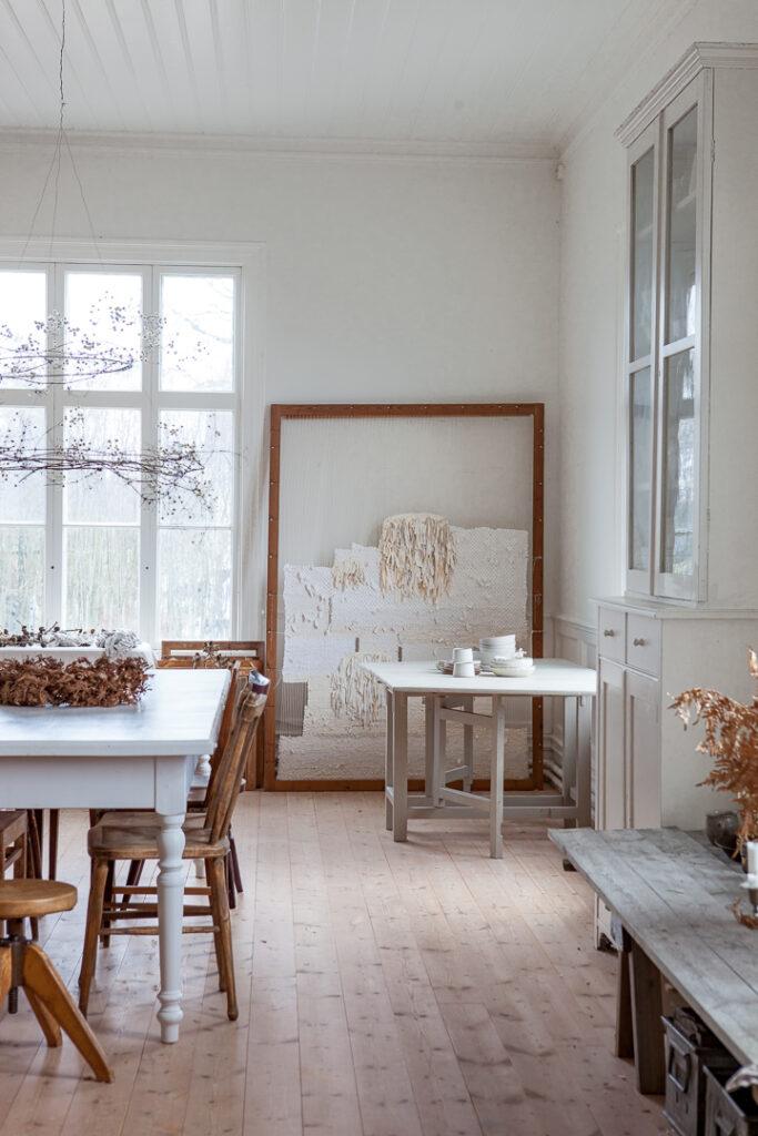Ateljen i vinterskrud dekorerad med naturmaterial som kransar av skogsklematis.