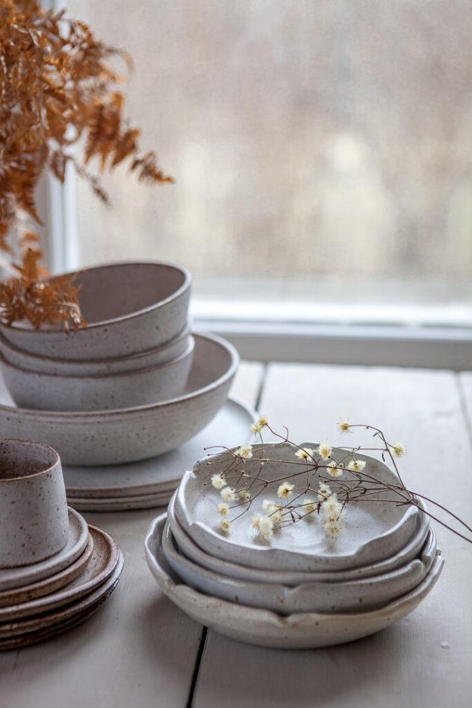 Keramik av Pia Ulfendahl och Luna Ceramic med en kvist av skogsklematis