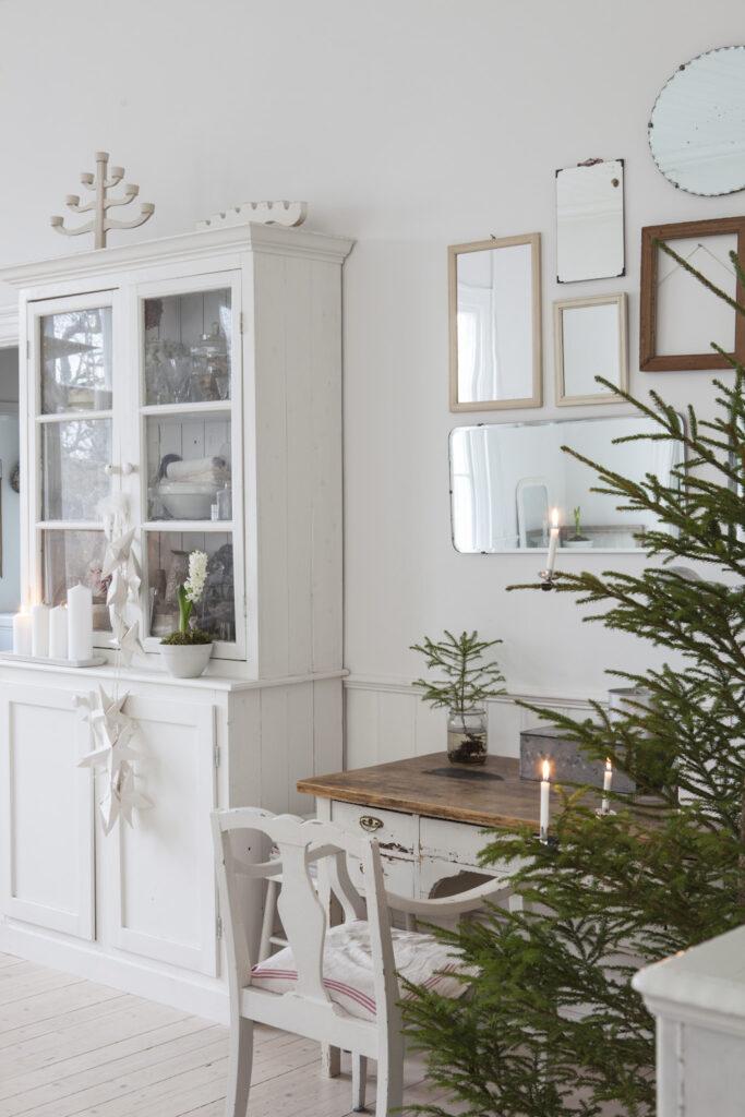 Gran med levande ljus och ett skåp i mitt julhem